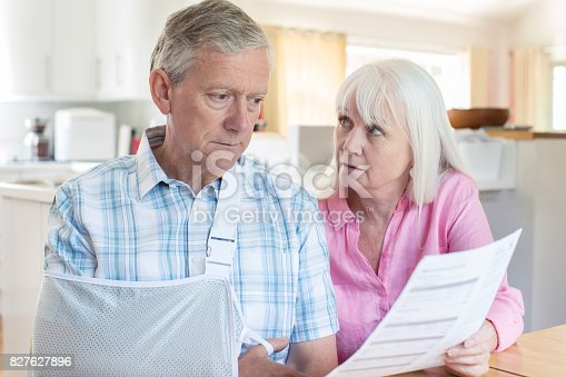 istock Couple Reading Letter About Husband's Injury 827627896