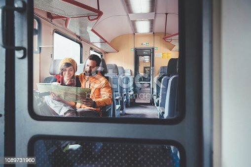 Couple traveling in train and using a map
