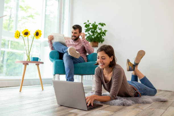 Couple reading newspapers and using laptop computer stock photo