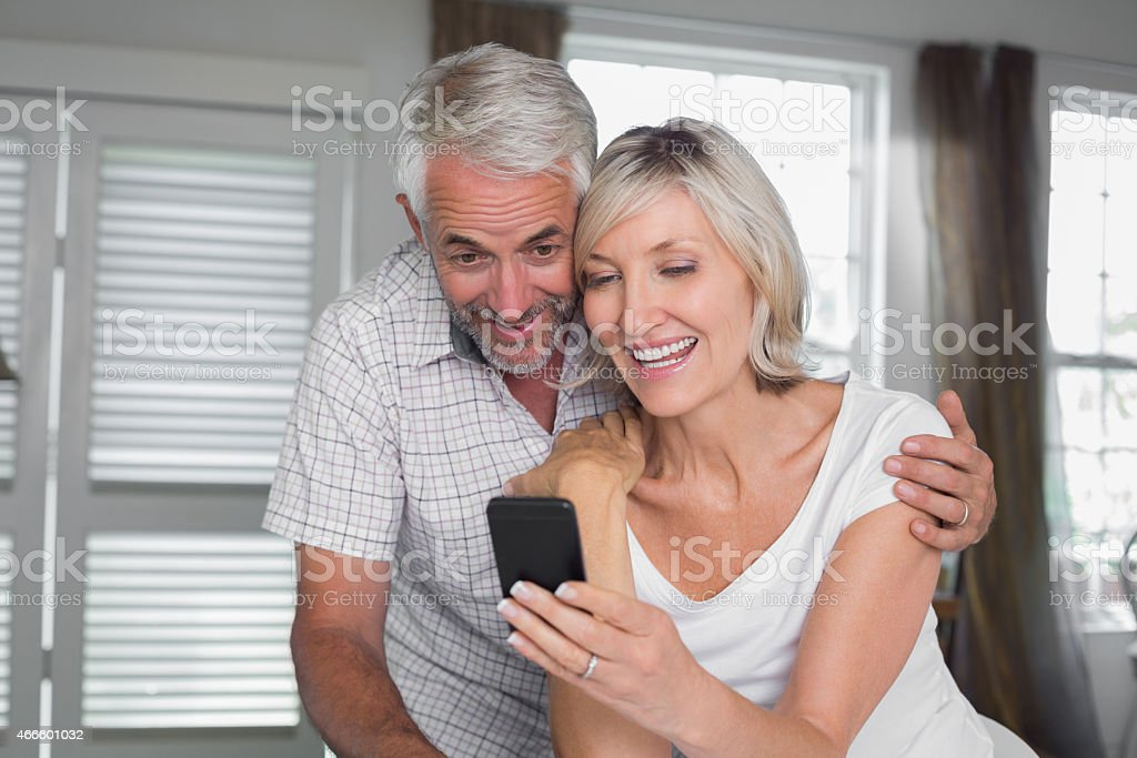 Couple reading text message at home stock photo