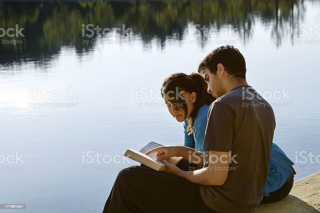 Couple Reading The Bible By A Lake stock photo