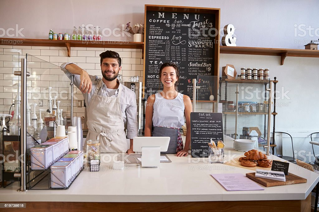 Couple ready to serve behind the counter of a coffee stock photo