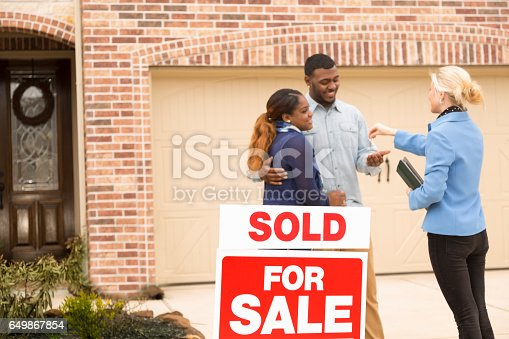istock Couple receives keys to first home real estate purchase. 649867854