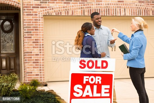 istock Couple receives keys to first home real estate purchase. 649871088