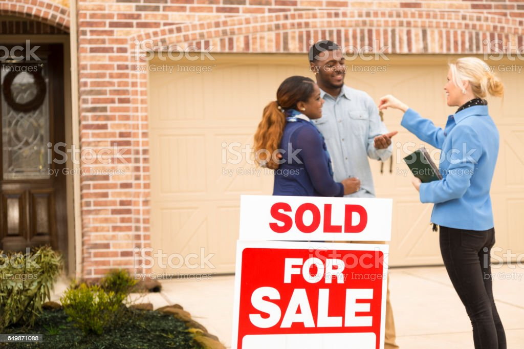 Couple receives keys to first home real estate purchase. stock photo