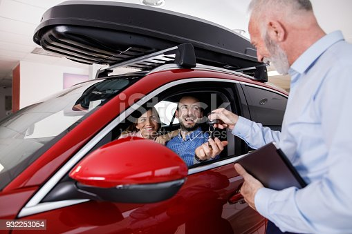 istock Couple receiving a new car keys from car salesperson 932253054