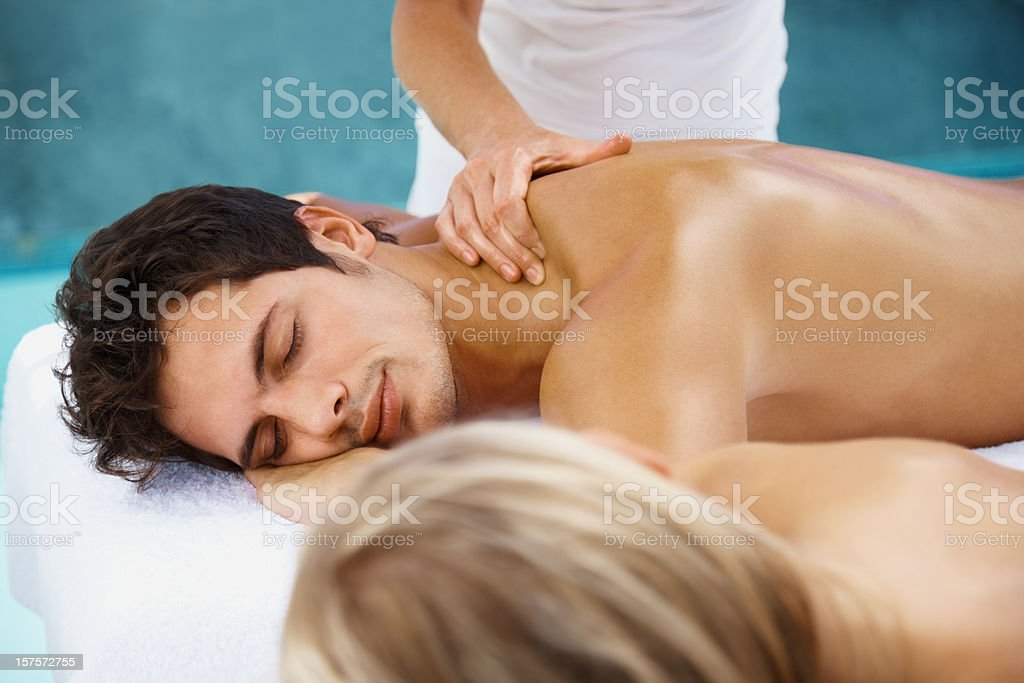 Couple receiving body massage and focus on the man royalty-free stock photo