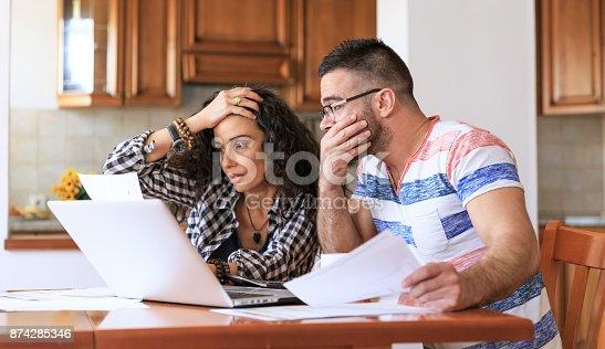 istock Couple receiving home bills 874285346