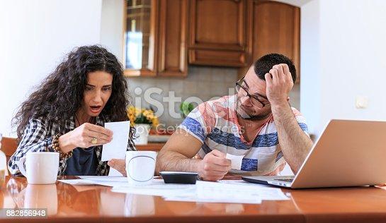 istock Couple receiving home bills 882856948