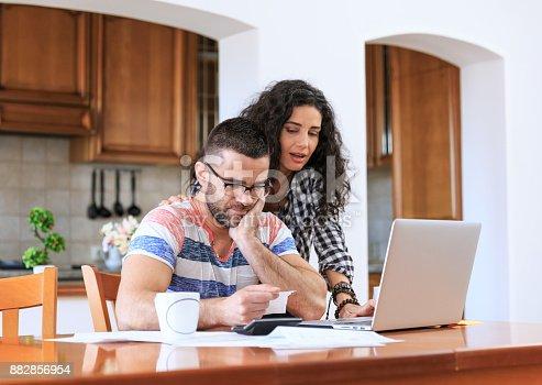istock Couple receiving home bills 882856954