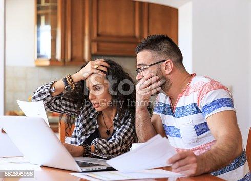 istock Couple receiving home bills 882856956