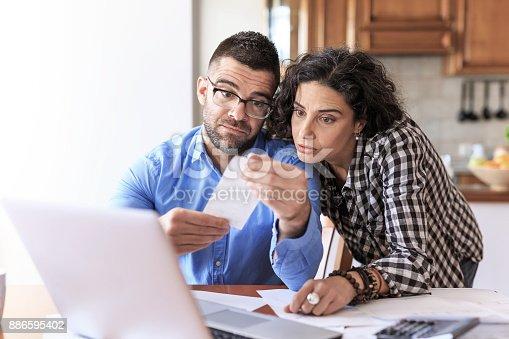 istock Couple receiving home bills 886595402