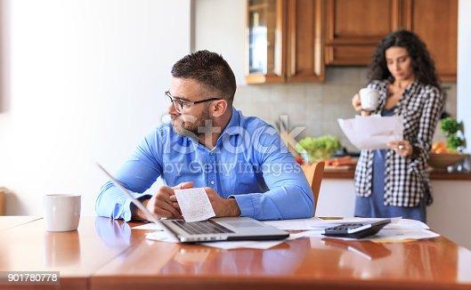 istock Couple receiving home bills 901780778