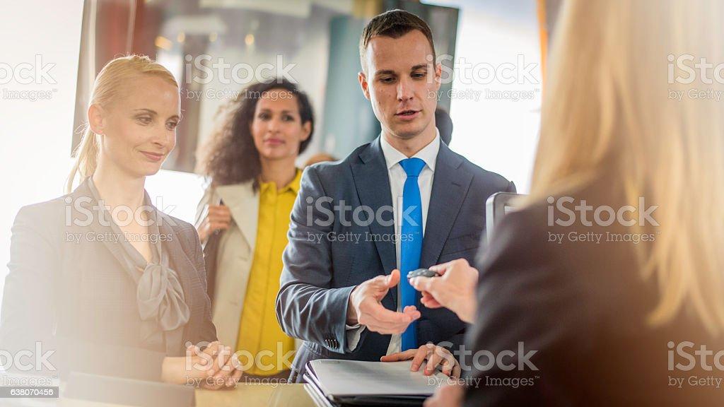 Couple receiving keys from car rental employee stock photo