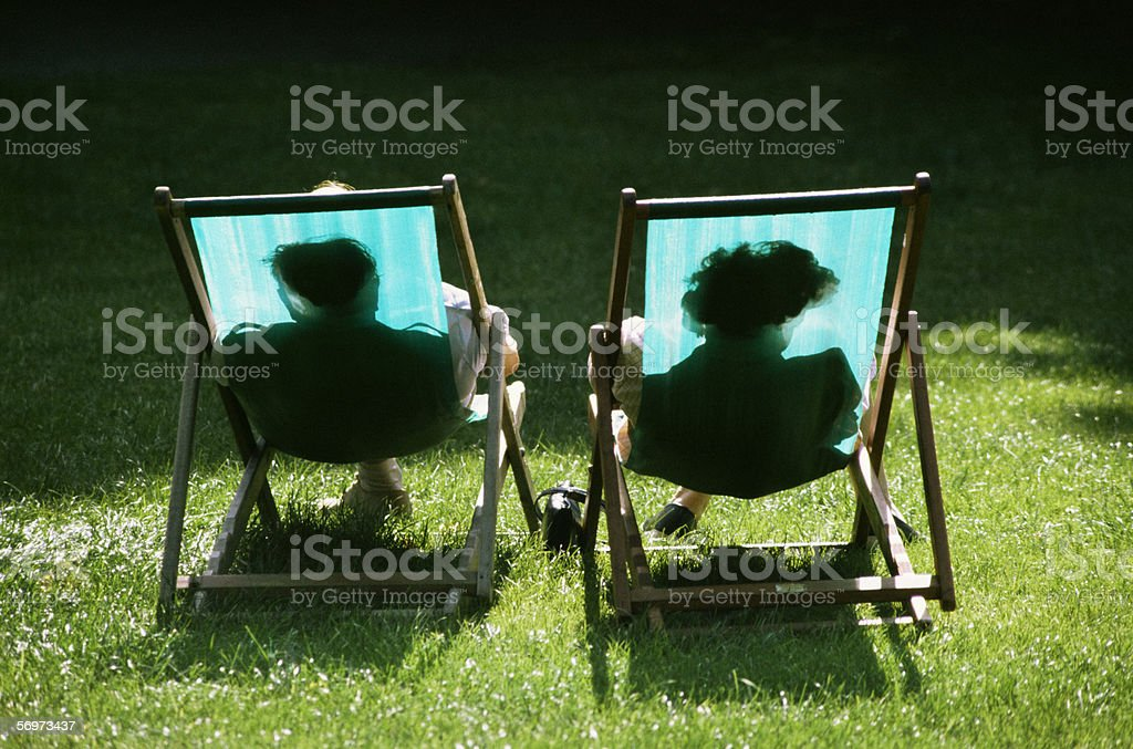 Couple reclining in deckchairs stock photo