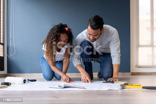 Happy African American couple redecorating their house and drawing on a blueprint