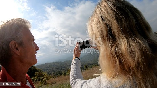 527894422 istock photo Couple relax against car while finding directions for their trip 1182215975