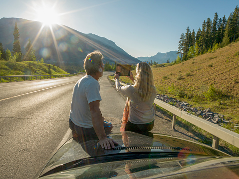 Couple relax beside car, taking pic with digital tablet