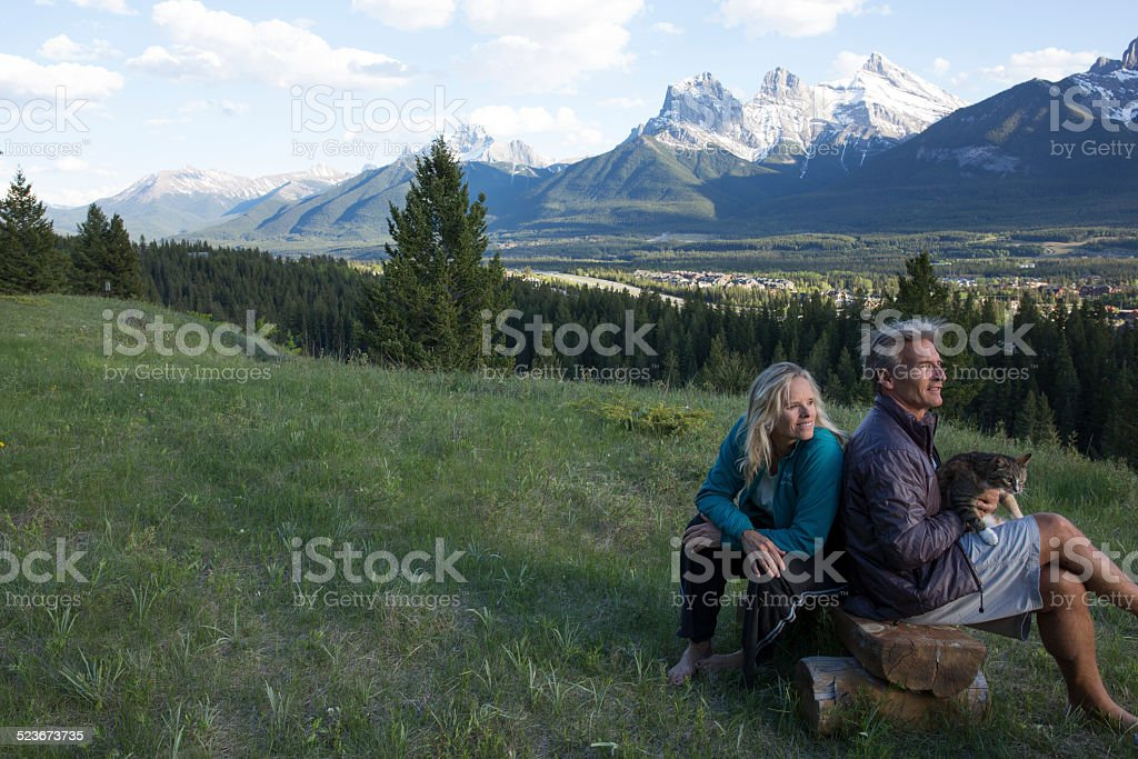 Couple relax on beach in meadow, with cat, mountains
