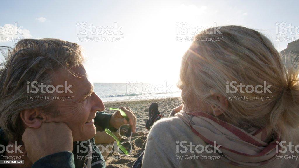 Couple relax on beach in sunlight stock photo
