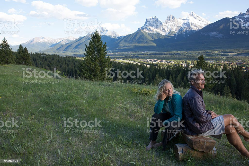 Couple relax on bench in meadow,, mountains stock photo