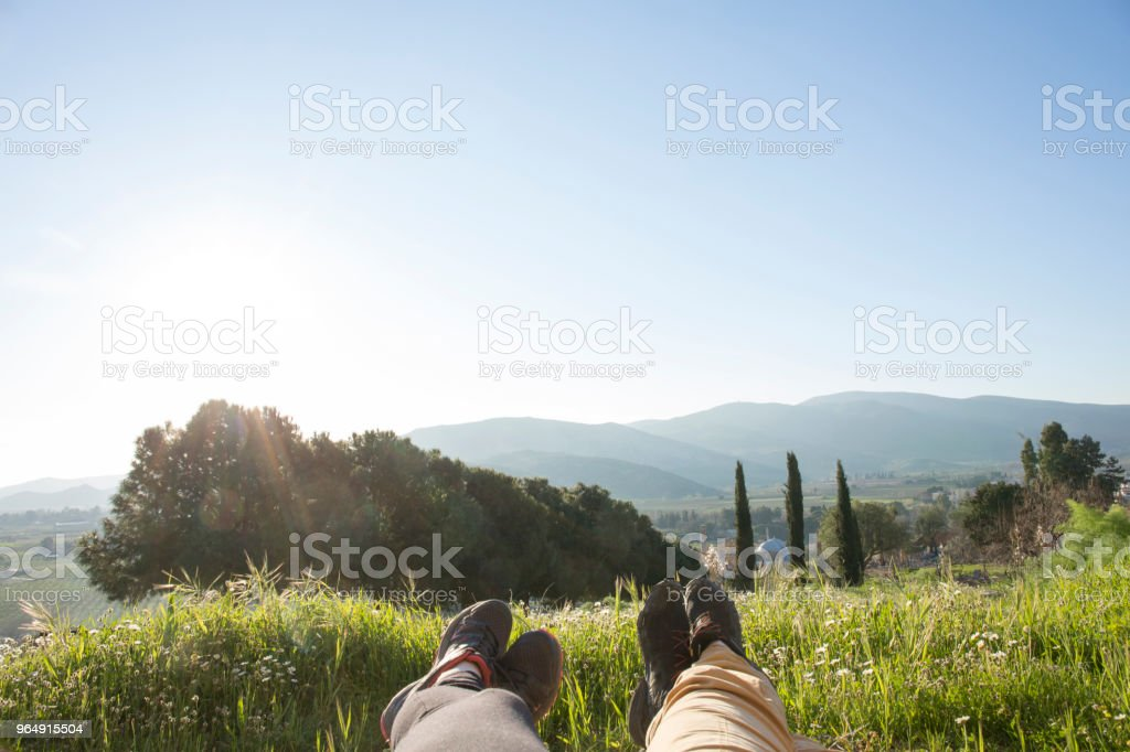 Couple relax on hill crest in sunlight royalty-free stock photo