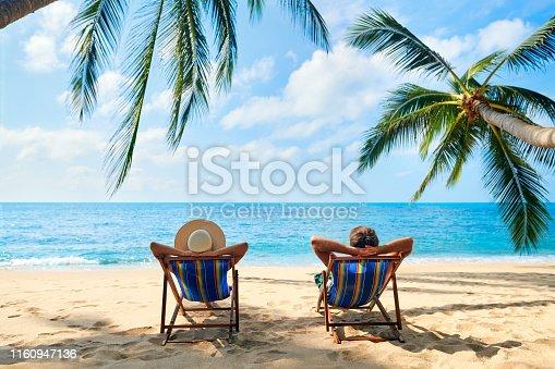 istock Couple relax on the beach enjoy beautiful sea on the tropical island 1160947136