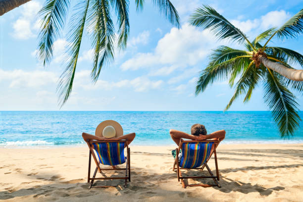 Couple relax on the beach enjoy beautiful sea on the tropical island Couple relax on the beach enjoy beautiful sea on the tropical island. Summer beach vacation concept travel stock pictures, royalty-free photos & images