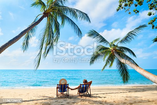 Couple relax on the beach enjoying beautiful sea on the tropical island. Summer beach vacation concept