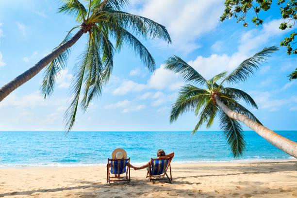 paar ontspannen op het strand genieten van prachtige zee op het tropische eiland - strandvakantie stockfoto's en -beelden