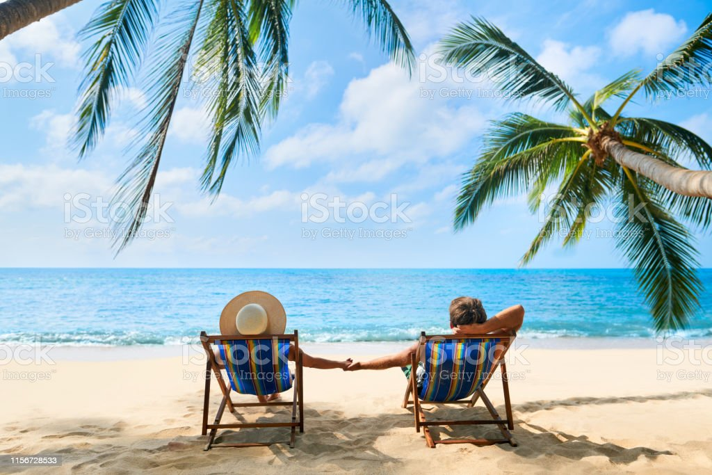 Pareja relajarse en la playa disfrutando de hermoso mar en la isla tropical - Foto de stock de Adulto libre de derechos