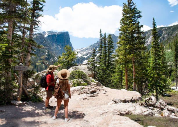 Couple relaxing and enjoying beautiful mountain view in Colorado. Couple relaxing and enjoying beautiful mountain view. Man and woman with backpacks hiking on Emerald Lake trail.Early summer landscape with snow covered mountains.Rocky Mountains National Park, USA emerald lake stock pictures, royalty-free photos & images