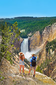Couple relaxing and enjoying beautiful view on vacation hiking trip. Man and woman with backpacks looking at  waterfall.  Beautiful Lower Falls at Yellowstone National Park. Wyoming, USA