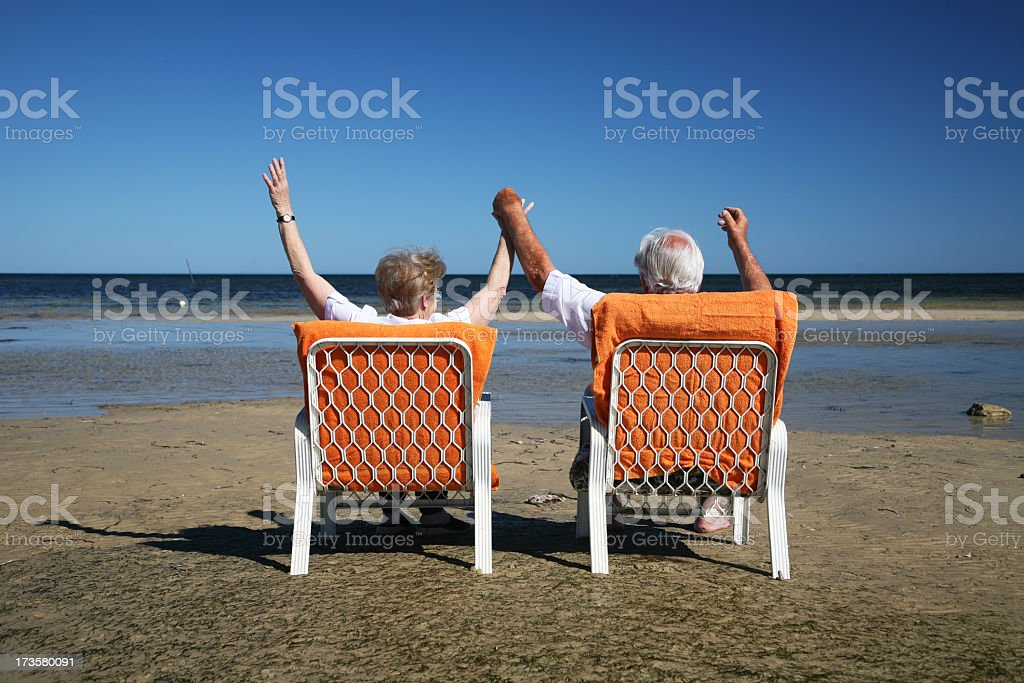 Couple relaxing and enjoying retirement at beach royalty-free stock photo