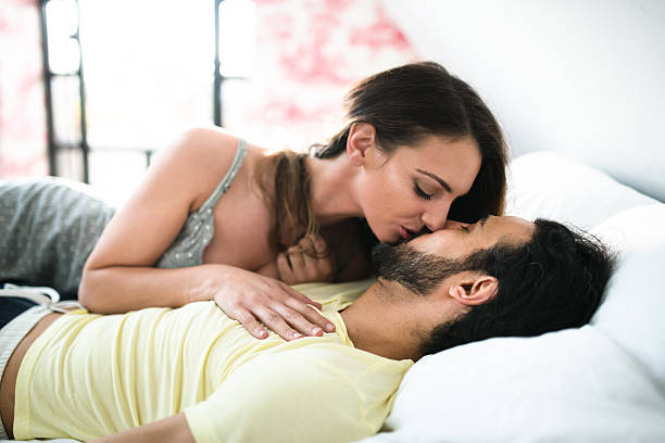 couple relaxing and kissing on the bed stock photo