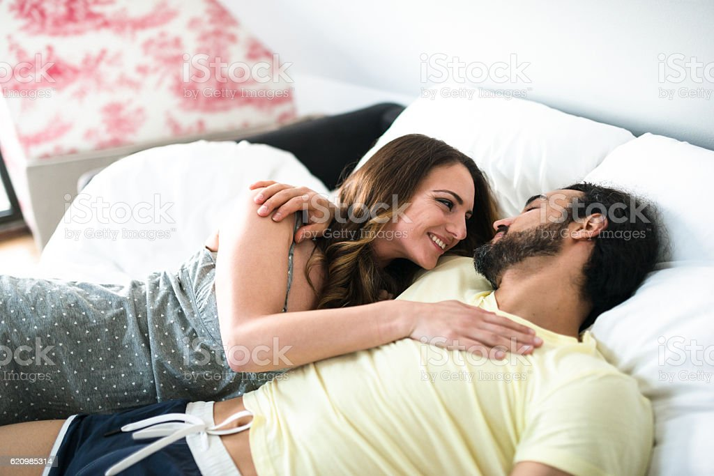 couple relaxing and kissing on the bed foto royalty-free