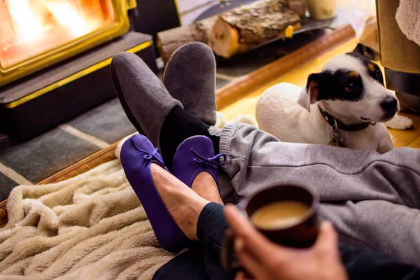 Couple relaxing at home near fireplace with legs crossed and slippers stock photo