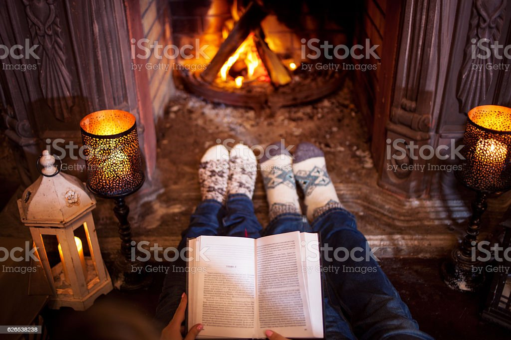 Couple relaxing at home reading a book. Feet in wool - foto de stock