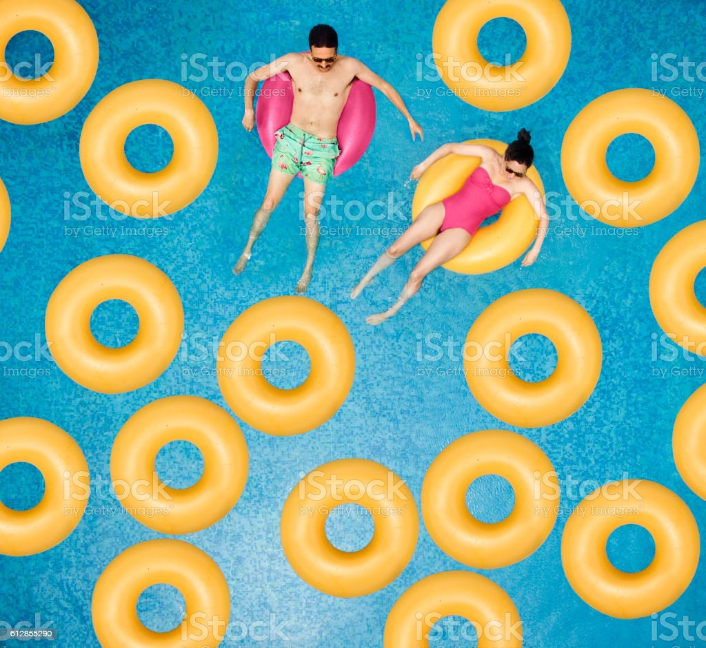 Couple relaxing at swimming pool stock photo