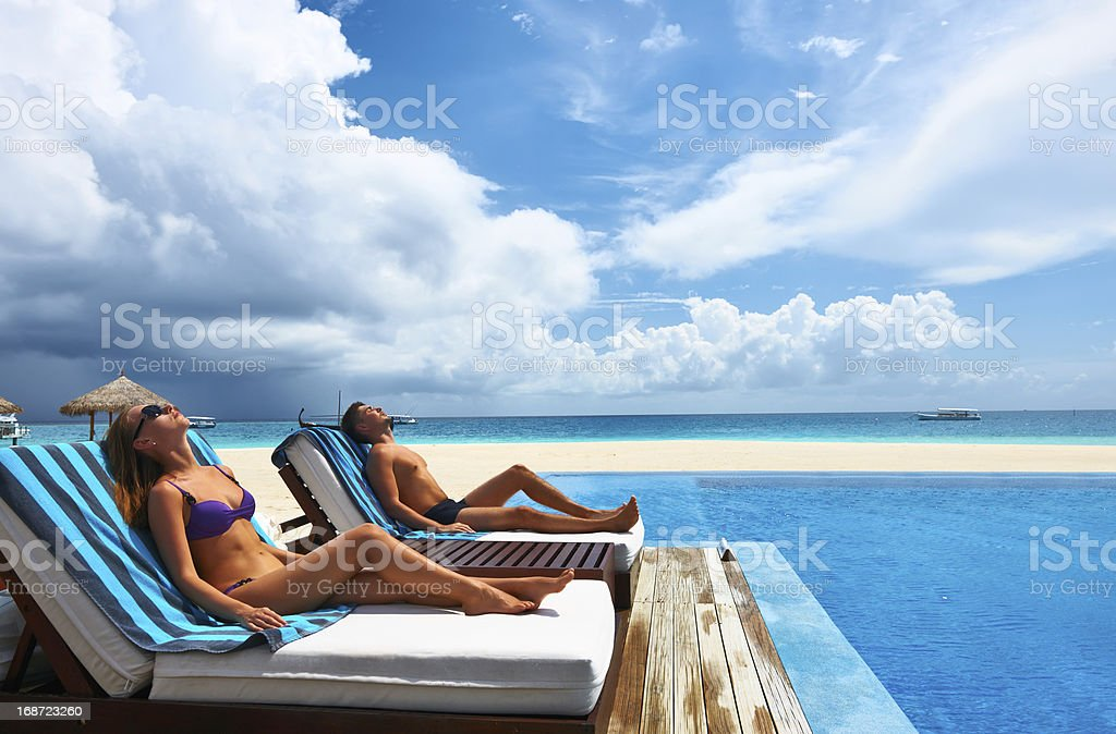 Couple relaxing at the poolside royalty-free stock photo