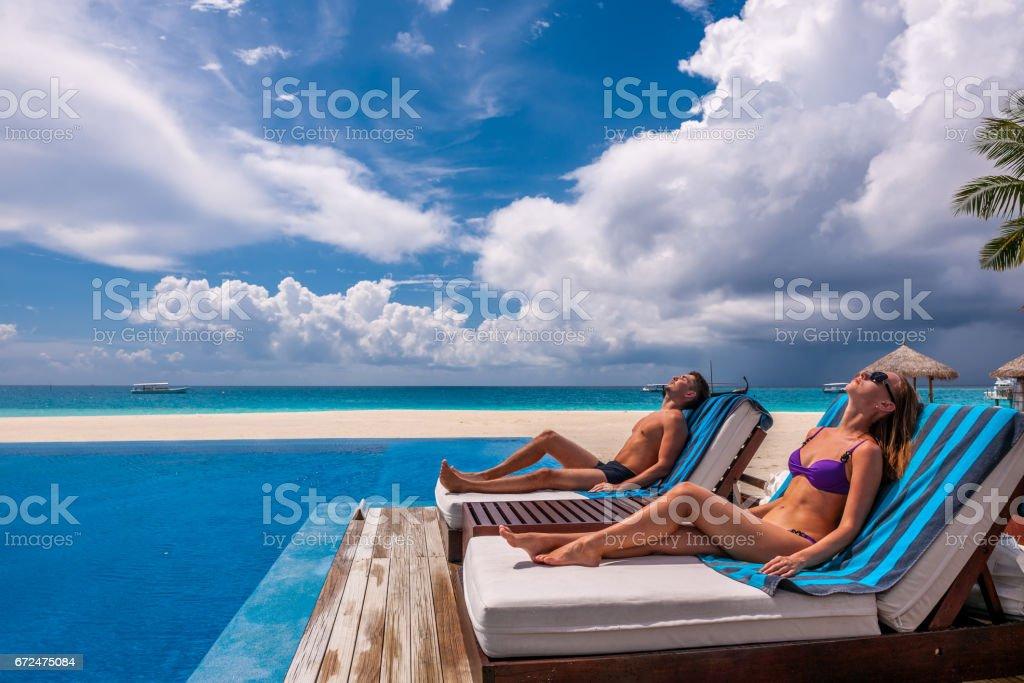 Casal relaxando à beira da piscina - foto de acervo