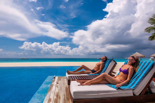 Couple relaxing at the poolside Couple relaxing in lounger at the poolside chaise longue stock pictures, royalty-free photos & images