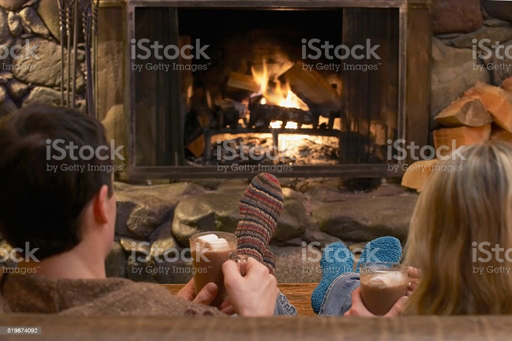 Couple relaxing by a fire stock photo