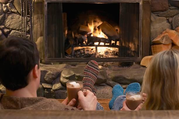 couple relaxing by a fire - station de ski photos et images de collection