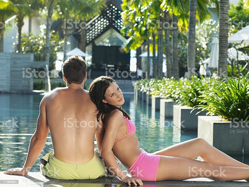 Couple relaxing by pool royalty-free stock photo