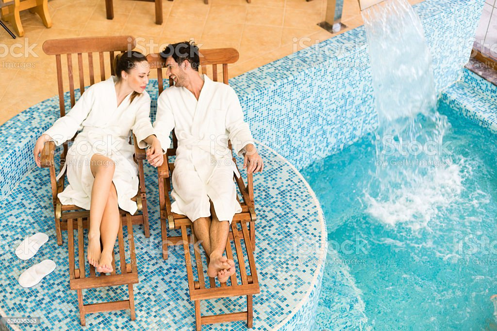 Couple relaxing by the swimming pool stock photo