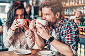 Beautiful young couple drinking coffee and looking each other