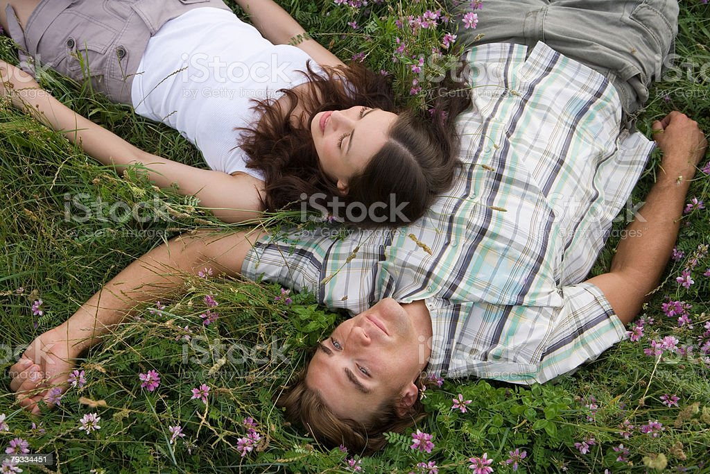 Couple relaxing in a field 免版稅 stock photo
