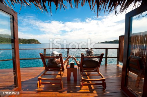 Couple relaxing on sun lounges in an over water bungalow