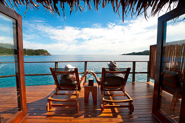couple relaxing in an over water bungalow - fiji stock photos and pictures